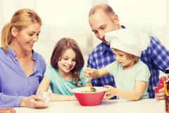 Stock Photo of happy family with two kids eating at home
