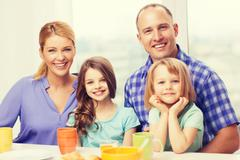Stock Photo of happy family with two kids with having breakfast
