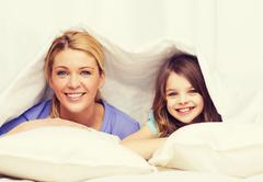 mother and little girl under blanket at home - stock photo