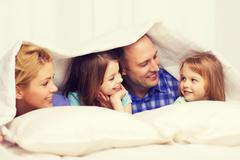 Stock Photo of happy family with two kids under blanket at home