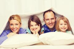 Happy family with two kids under blanket at home Stock Photos