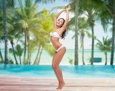 happy young woman in bikini dancing on beach - stock photo