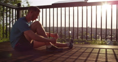 A young jogger tying his running shoes and admiring the view. Stock Footage