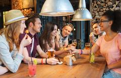 Stock Photo of happy friends with drinks talking at bar or pub