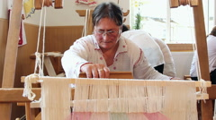 A woman weaves at an old wooden loom Stock Footage