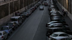 Cars driving down a narrow street with cars parked along both sides. Stock Footage