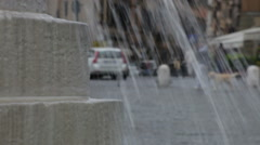 Artistic view through fountain water of people traveling - stock footage