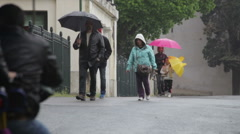 Tourists traveling down a rainy road in Rome Stock Footage