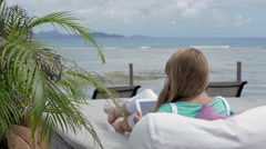 Woman in deckchair using digital tablet during exotic vacation. Stock Footage