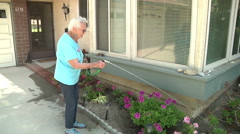 Active Senior Woman Watering Plants Outdoors  Daily Life Retirement Community Stock Footage