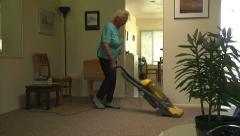Active Senior Woman Vacuuming Carpet Cleaning Live  Alone Daily Life Retirement Stock Footage