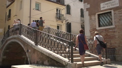 People walking over love locks bridge at Campiello Drio La Pieta Stock Footage