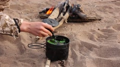 Female hiker mixing tea in a pot at camp site bonfire - stock footage