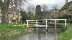 Springtime Footbridge over River Eye in Lower Slaughter Village in the Cotswo Stock Footage