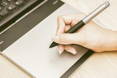 Retro image of female hand of a designer drawing with the stylus on a grey gr - stock photo