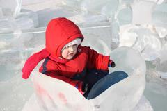 Little girl wearing warm jumpsuit sits in ice nenuphar at winter outdoor - stock photo