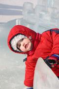 Little girl wearing warm jumpsuit in ice town at winter outdoor - stock photo