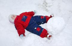 Little tired girl wearing warm jumpsuit lies on snow near big snowball - stock photo