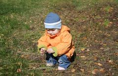 Little girl wearing orange jacket sits and plays with fir cones in forest - stock photo