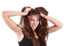 Young angry woman tears her hair and looks at camera isolated on white backgr - stock photo