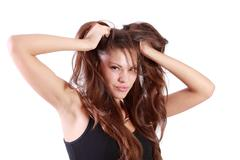 Young brunette woman tears her hair and looks at camera isolated on white bac - stock photo