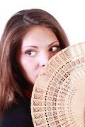 Young woman looks away and hides her mouth by fan isolated on white backgroun Stock Photos
