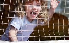 Little beautiful happy girl shouts at playground with grid. Stock Photos