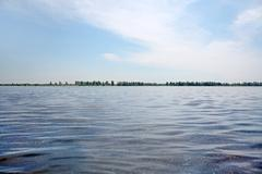 Deep blue waters of river and poplar down on water, blue sky with clouds. - stock photo