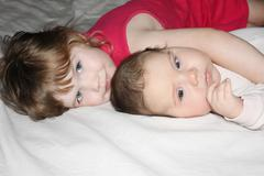Little beautiful baby and pretty girl lies on white sheet on bed. Focus on bo - stock photo