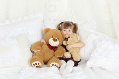 Little girl sits on double bed with many pillows and teddy bears and smiles. - stock photo