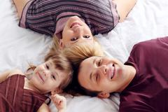 Happy father, little daughter and mother lie on white double bed and look up. Stock Photos