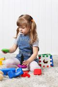 Happy little girl gathers pyramid among multi-colored toys on soft carpet at  - stock photo