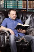 Smiling man sits in leather armchair and reads book next to shelves with lots - stock photo