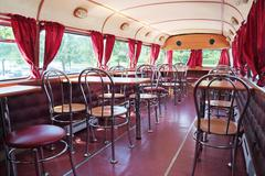 PERM, RUSSIA - JUN 11, 2013: Tables in double-decker bus cafe Kentucky Fried  - stock photo