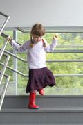 Little girl with two pigtails holding railing down stairs Stock Photos