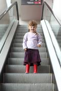 Stock Photo of Little girl with pigtails and gumboots coming down escalator