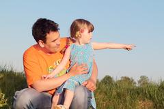 Father and daughter sitting in meadow and look in one direction - stock photo