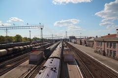 Many long passenger and freight trains at railway station in sunny day - stock photo