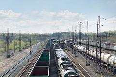 Many long freight trains at railway station with many wires at summer day. Ab - stock photo