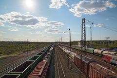 Stock Photo of Sun and freight trains at railway station with old railroads at summer day. A