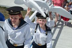 Stock Photo of PERM, RUSSIA - JUN 15, 2013: Girls in suits of sailors carry white gulls. Mil