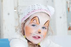 Little beautiful girl with face painting of orange fox poses in hat Stock Photos