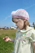 Little girl looks at blade of grass village at summer sunny day - stock photo