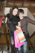 Young beautiful girl and boy rise on escalator with shopping bags in mall. Stock Photos