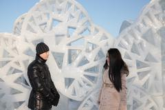 Young  boy and girl stand near ice wall with triangular holes and look at eac - stock photo