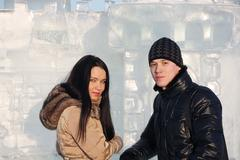 Young beautiful couple stand neat ice wall at sunny winter day. - stock photo