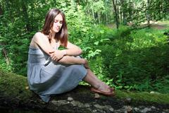 Beautiful girl in dress with long hair sits on fallen tree in forest - stock photo