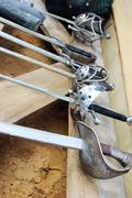 Row of six hilts of rapiers on wooden boards and sand. closeup Stock Photos