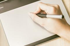 Retro image of female hand of a designer drawing with the stylus on a grey gr Stock Photos