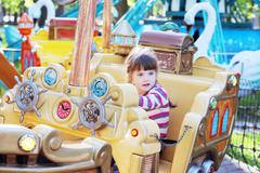 Pretty smiling little girl ride on carousel pirate ship in summer park - stock photo
